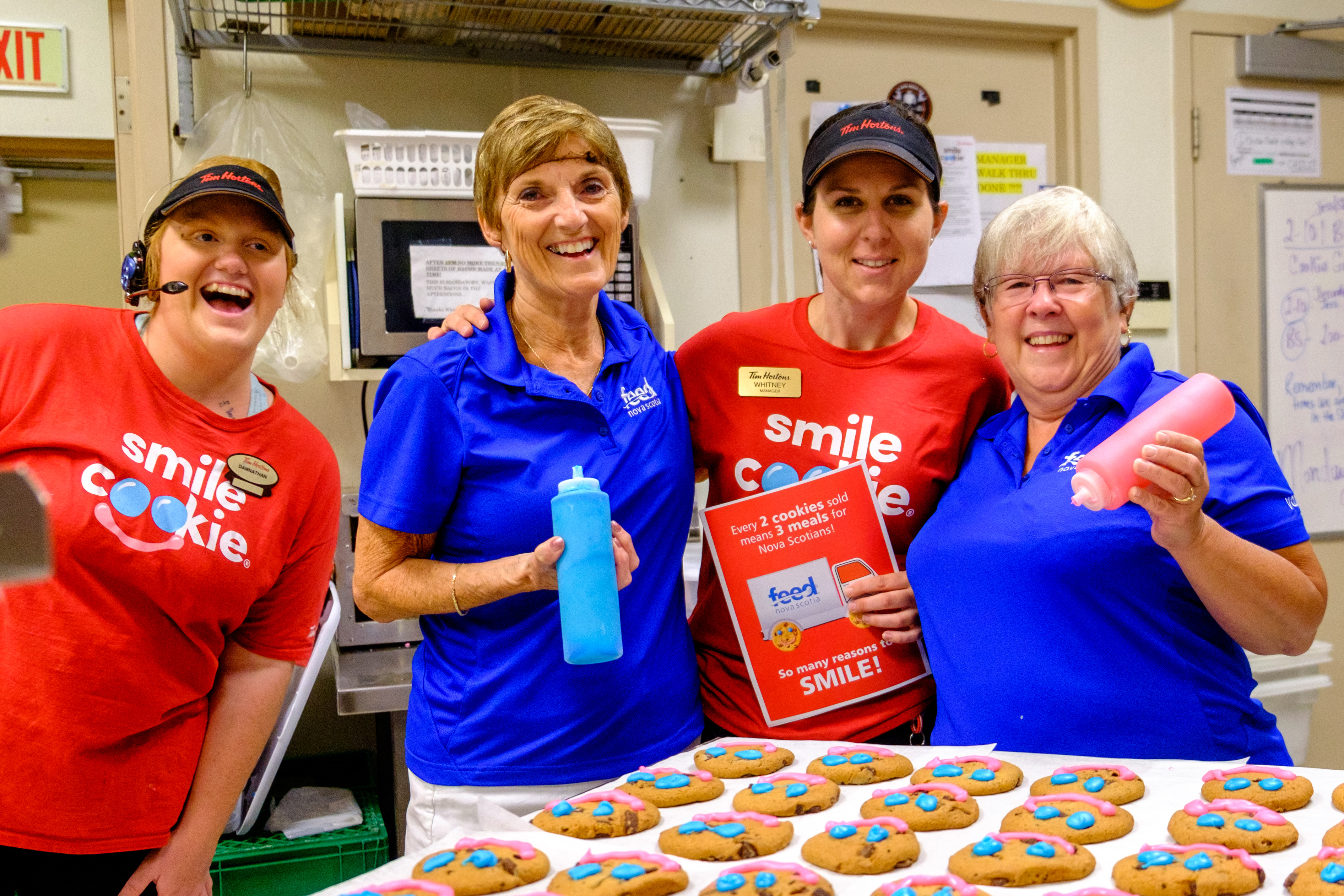 Feed Nova Scotia volunteers and Tim Hortons staff posing with Smile Cookies