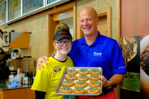 two people smiling holding a tray of chocolate chunk cookies