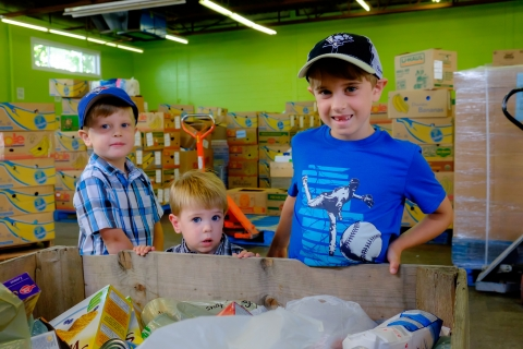 Three young boys standing in front of a box filled with food