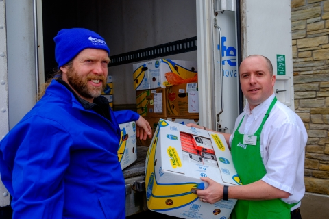 Two men holding boxes of food one wearing a Feed Nova Scotia attire and one a Sobey's uniform