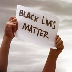 Person holding poster with the words Black Lives Matter
