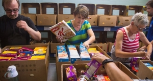 Four people sorting food within Feed Nova Scotia boxes