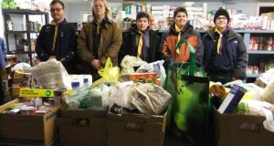 Five scouts stand with bags and boxes of non-perishable food