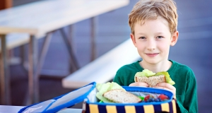 boy at school eating a sandwich from a lunch box