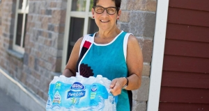 woman holding a case of bottled water