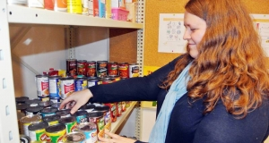 Woman stacking cans of food on a shelf