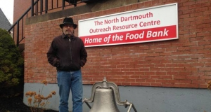 Kevin Clarke, president of North Dartmouth Outreach Resource Centre standing next to the sign outside the centre