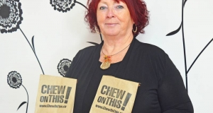 Woman holdling paper bags bearing a campaign logo