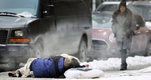 A pedestrian walks near a sleeping homeless person.