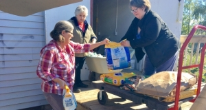 Food bank volunteers receiving a delivery of pet food