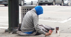 a homeless person sitting on the sidewalk asking for change