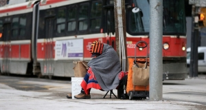 homeless person sitting on a sidewalk