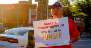 Man holding a placard about hunger awareness