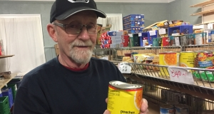 Robert Dolomont holding a dented can of peaches