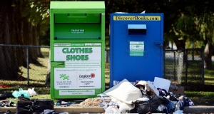 Two large non-profit donation bins with debris around them